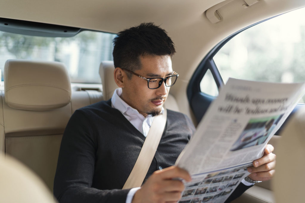 Photo of passenger in vehicle reading newspaper.