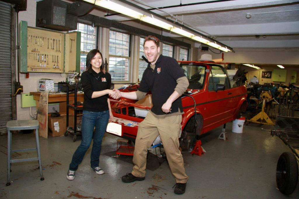 Image of teacher and student in front of VW Cabriolet being converted to electric power.