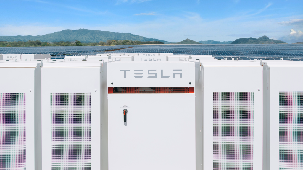 Photo of Tesla PowerPack with solar panels in background.
