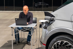 Image of person using laptop plugged in to Hyundai Ioniq 5's Level 2 charging port.